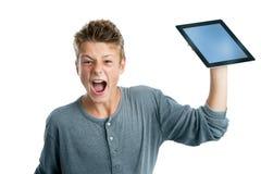 Adolescente enojado alrededor para romper la tableta. Foto de archivo
