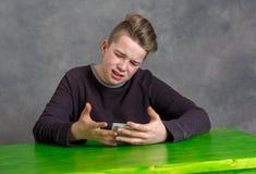 Adolescente enojado con smartphone Foto de archivo libre de regalías