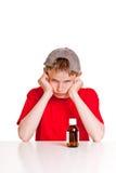Adolescente enojado detrás de la botella de la medicina Imagenes de archivo