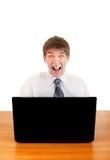Adolescente enojado detrás del ordenador portátil Imágenes de archivo libres de regalías