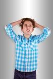 Adolescente enojado en fondo gris Imagen de archivo