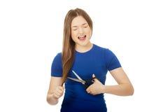 Adolescente enojado que corta su pelo Imagen de archivo libre de regalías