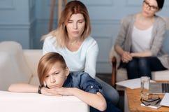 Adolescente enojado que miente en la parte de atrás del sofá Imagen de archivo libre de regalías