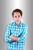 Adolescente enojado que mira delante de sus ojos con sus brazos doblados Imagen de archivo libre de regalías