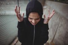 Adolescente enojado que se coloca en el campus de la escuela Imagenes de archivo
