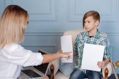 Adolescente enojado que sostiene dos hojas de papel Imágenes de archivo libres de regalías