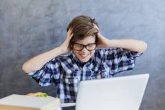 Adolescente enojado que trabaja en el ordenador portátil en casa Imagen de archivo libre de regalías