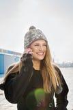 Adolescente enthousiaste parlant au téléphone dehors Image stock