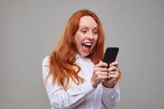 Adolescente entusiasta con un teléfono móvil en manos Foto de archivo