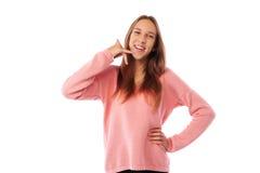 Adolescente entusiasta que imita una llamada de teléfono con su mano mientras que Fotografía de archivo libre de regalías