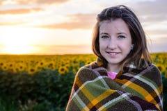 Adolescente envuelto en manta en campo del girasol Imágenes de archivo libres de regalías