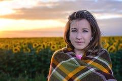 Adolescente envuelto en manta en campo del girasol Fotos de archivo