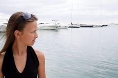 Adolescente está cerca de los barcos de mar Fotografía de archivo libre de regalías