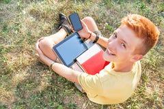 Adolescente está con la tableta y el teléfono elegante Imagen de archivo libre de regalías