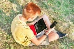 Adolescente está con la tableta y el teléfono elegante Imagen de archivo