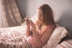 Adolescente está mintiendo en cama en sol y la mirada de la mañana Fotografía de archivo libre de regalías