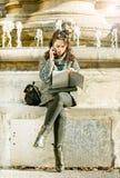Adolescente/estudiante joven que mira su cuaderno y que habla en el teléfono Imágenes de archivo libres de regalías