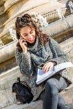 Adolescente/estudiante joven que mira su cuaderno y que sonríe - tiro dinámico Foto de archivo libre de regalías