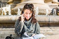 Adolescente/estudiante joven que mira su cuaderno y sonrisa Foto de archivo