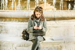 Adolescente/estudiante joven que mira su smartphone Imágenes de archivo libres de regalías