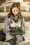 Adolescente/estudiante joven que mira su smartphone - tiro cercano Foto de archivo libre de regalías