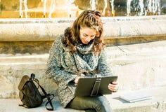 Adolescente/estudiante joven que mira su tableta Foto de archivo libre de regalías