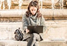 Adolescente/estudiante joven que mira su tableta - vista delantera Imagenes de archivo