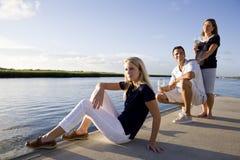 Adolescente et parents sur le dock par la détente de l'eau image libre de droits