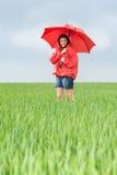 Adolescente exaltado que sostiene el paraguas rojo Fotografía de archivo