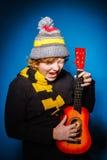 Adolescente expresivo pelirrojo que juega en ukalele Fotografía de archivo