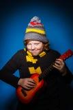 Adolescente expresivo pelirrojo que juega en ukalele Fotografía de archivo libre de regalías