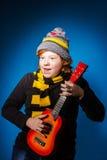 Adolescente expresivo pelirrojo que juega en ukalele Fotos de archivo libres de regalías