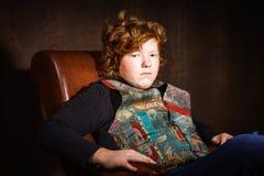 Adolescente expresivo pelirrojo que se sienta en butaca Foto de archivo