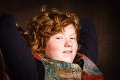 Adolescente expresivo pelirrojo que se sienta en butaca Imagenes de archivo