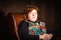 Adolescente expresivo pelirrojo que se sienta en butaca Fotografía de archivo libre de regalías