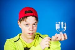 Adolescente expresivo que presenta con el vidrio de agua Imagen de archivo libre de regalías