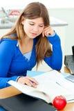 Adolescente fêmea alegre que estuda na cozinha Imagens de Stock