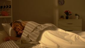 Adolescente fêmea que acorda na cama que sorri, bom humor na manhã, positividade filme