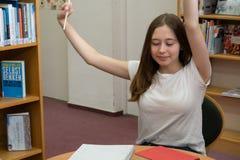 Adolescente fatigu?e ?tudiant dans la biblioth?que image libre de droits