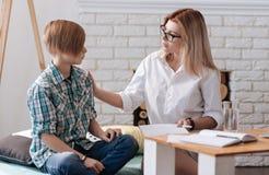 Adolescente favorable del spsychologist femenino profesional serio Foto de archivo libre de regalías