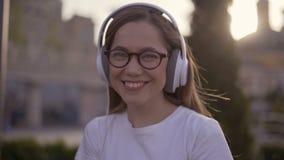 Adolescente felice che ascolta la musica sulle cuffie in parco di estate 4K video d archivio