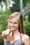 Adolescente felice che indica alla macchina fotografica fotografia stock
