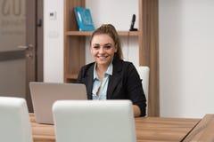 Adolescente felice che lavora al computer portatile in biblioteca Immagine Stock Libera da Diritti