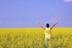 Adolescente felice che sta in un campo della colza fotografia stock