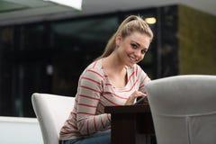 Adolescente felice che utilizza il cuscinetto di tocco nel caffè Immagine Stock