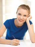 Adolescente felice con la penna e la carta Fotografia Stock
