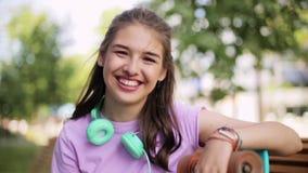 Adolescente felice con le cuffie e il longboard archivi video