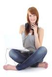 Adolescente felice con le cuffie e la seduta del computer portatile Fotografia Stock
