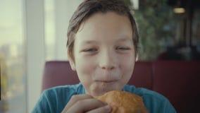 Adolescente felice del metraggio giovane che mangia hamburger saporito in fast food archivi video