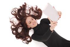 Adolescente felice dello studente che si trova sul pavimento che esamina compressa Immagini Stock Libere da Diritti